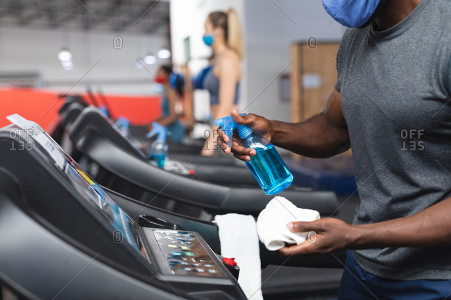 Mid section of fit African American man wearing face mask sanitizing cardio machine before working out in the gym.