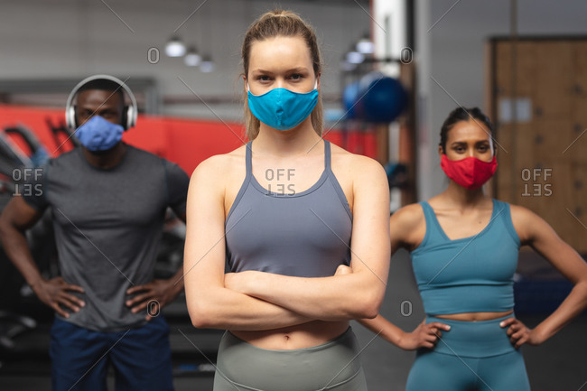 Portrait of fit African American man and two fit caucasian woman wearing face masks standing in the gym.