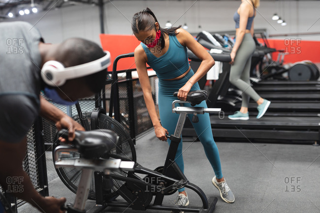 Fit African American man and fit caucasian woman wearing face masks adjusting seat of stationary bike in the gym.