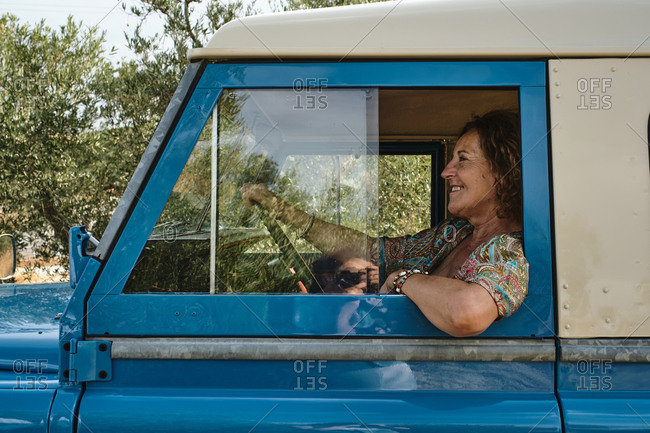 Low angle side view of carefree mature female sitting on driver seat of old automobile parked in village and looking away