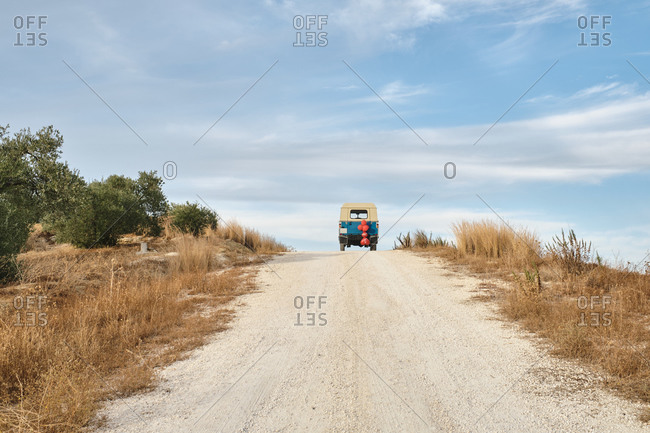 Lonely car driving along rural sandy roadway in summer on background of blue sky