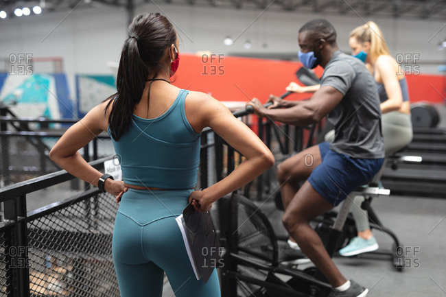 Fit African American man wearing face mask exercising on stationary bike while caucasian female fitness coach with clipboard inspecting in the gym.