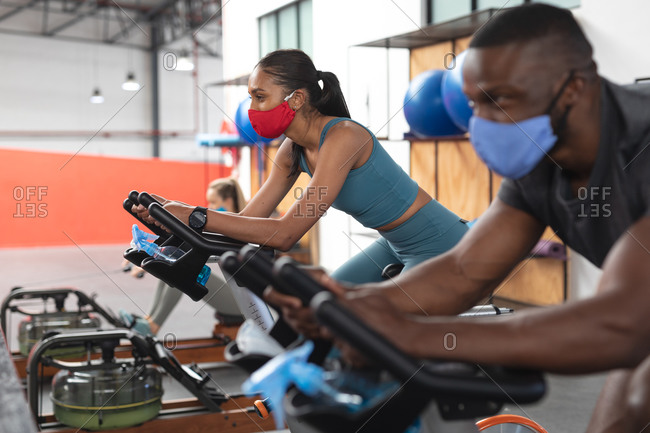 Fit African American man and fit caucasian woman wearing face masks exercising on stationary bike in the gym.