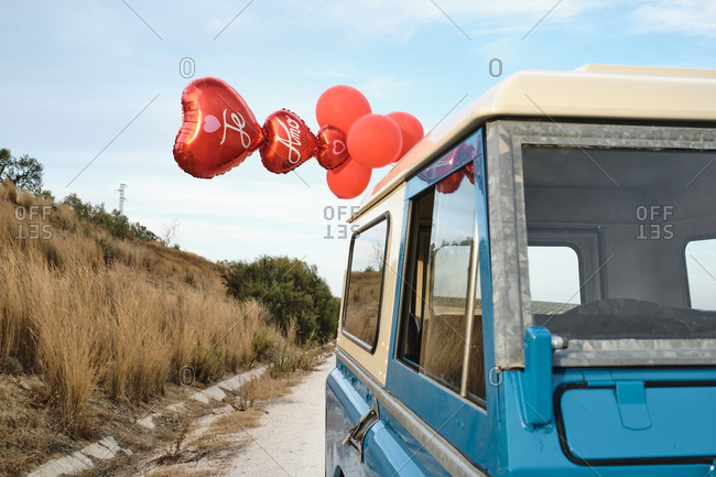 Low angle of vintage shiny car with red air balloons in shape of heart parked on sandy road in countryside
