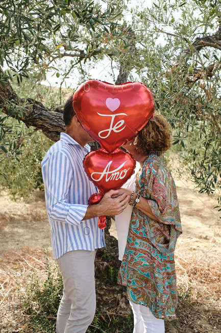 Side view of unrecognizable couple standing together near tree in garden and hiding behind red air balloons in shape of heart