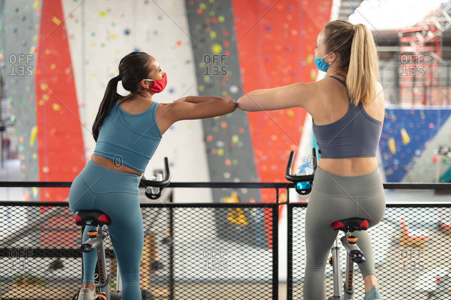 Rear view of two fit caucasian woman wearing face masks greeting each other by touching elbows while exercising on stationary bike in the gym.