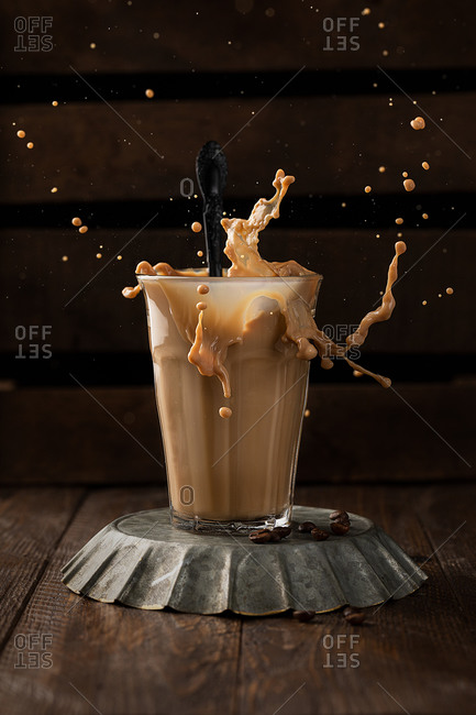 Glass of aromatic coffee with milk splashing above wooden table in coffee shop