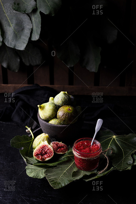 High angle of homemade jam in glass jar made of ripe fresh figs placed on table in garden