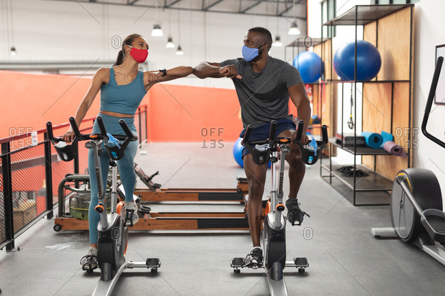 Fit African American man and fit caucasian woman wearing face masks greeting each other by touching elbows while exercising on stationary bike in the gym.