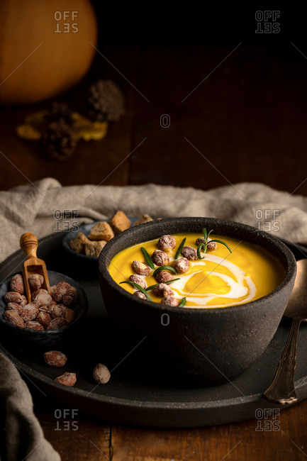 Nutritious pumpkin soup in bowl served on tray with crispy bread croutons and nuts on wooden table
