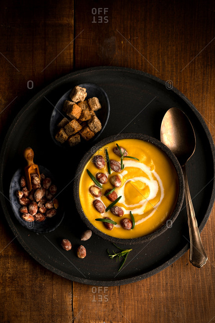 Top view of nutritious pumpkin soup in bowl served on tray with crispy bread croutons and nuts on wooden table
