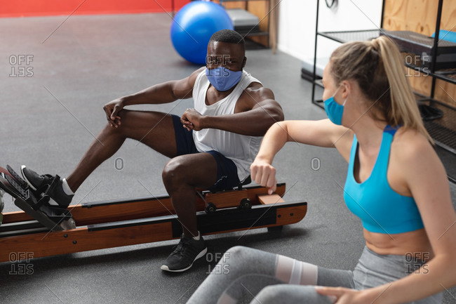 Fit African American man and Fit caucasian woman wearing face masks greeting each other by touching elbows while exercising in the gym.