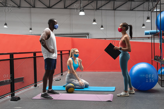 caucasian female fitness trainer holding stopwatch and clipboard instructing fit African American man and fit caucasian woman in the gym.