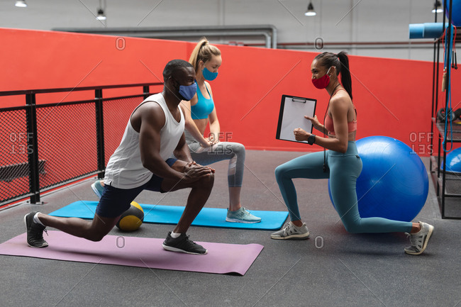 caucasian female fitness trainer holding stopwatch and clipboard instructing fit African American man and fit caucasian woman to perform stretching exercise in the gym.