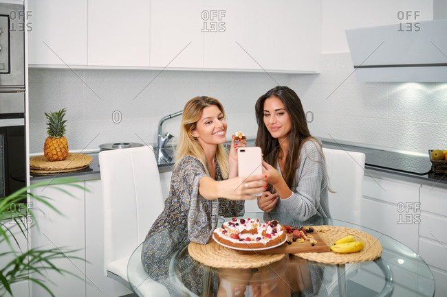 Smiling young female food bloggers with pieces of yummy vegan cake in hands taking selfie