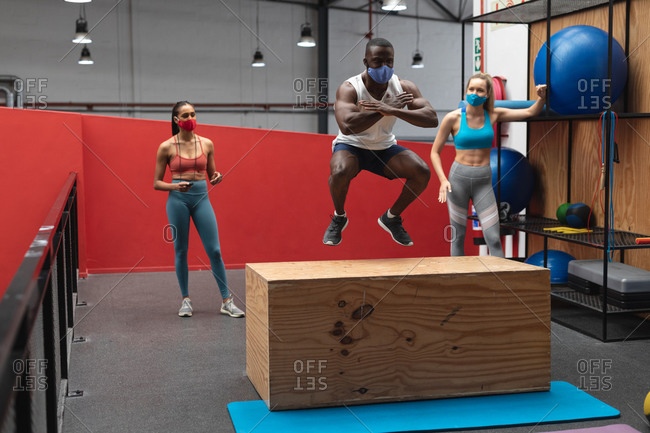 Fit African American man wearing face mask jumping on wooden plyo box in the gym while caucasian female fitness trainer holding stopwatch.