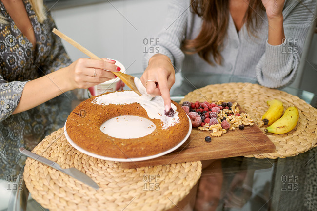 Crop anonymous female friends garnishing baked vegan banana cake with topping and fresh berries and nuts in home kitchen