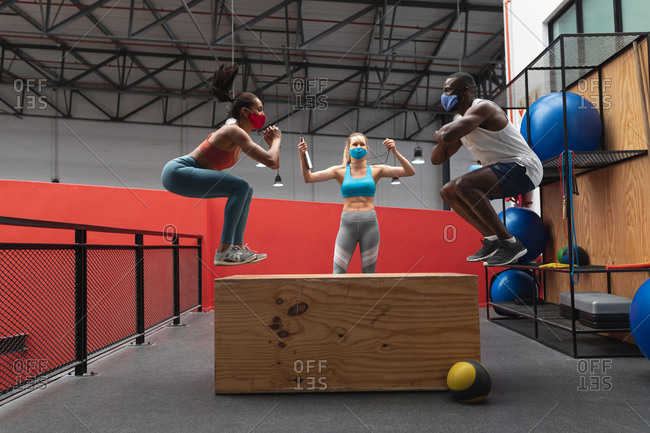 Fit African American man and Fit caucasian woman wearing face masks jumping on wooden plyo box in the gym while caucasian female fitness trainer holding stopwatch and clipboard.