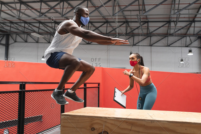 Fit African American man wearing face mask jumping on wooden plyo box in the gym while caucasian female fitness trainer holding stopwatch and clipboard.