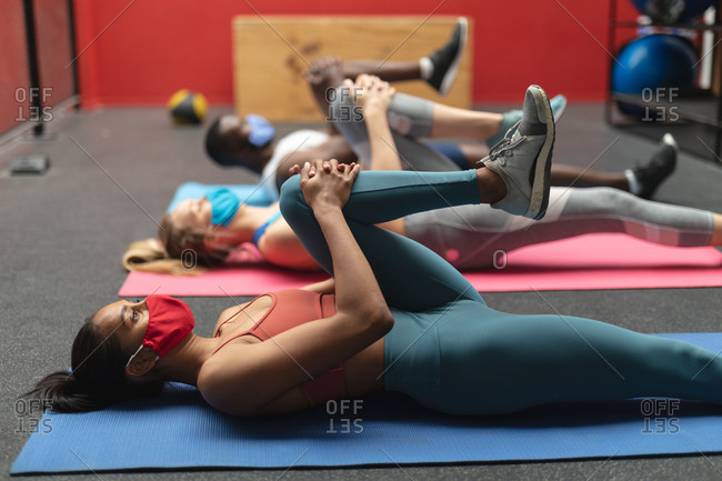 Fit African American man and two Fit caucasian woman wearing face masks performing stretching exercise while lying on yoga mats in the gym.