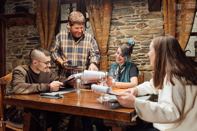 Cheerful friendly hipsters ordering food in rustic cafe while sitting together at wooden table