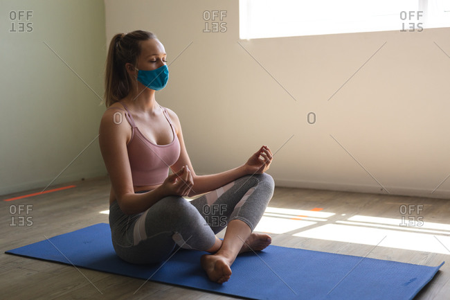Fit woman caucasian wearing face mask practicing yoga while sitting on yoga mat in the gym.