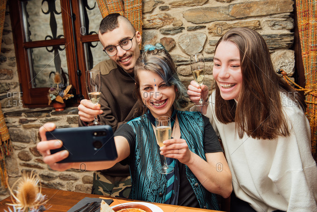 Delighted company of hipsters with fancy appearance sitting at table in cafe and taking selfie on smartphone while spending weekend together and having fun