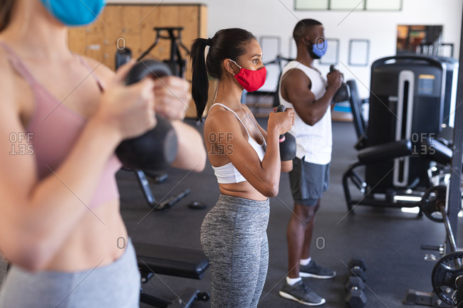 Fit African American man and two Fit caucasian woman wearing face masks performing exercise with kettlebells in the gym.