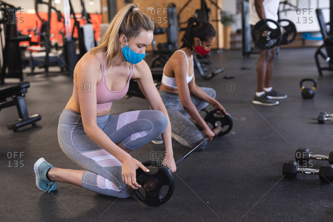 Two Fit caucasian woman wearing face masks adding weights in barbell in the gym.
