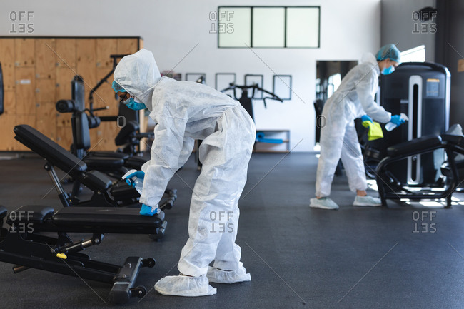 Team of workers wearing protective clothes and face masks cleaning the gym using disinfectant.