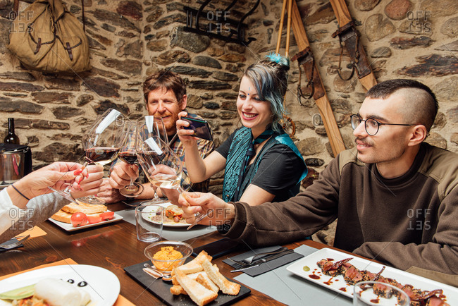 High angle of company of friendly hipsters gathering at wooden table in cafe and clinking glasses with champagne while smiling and relaxing at weekend