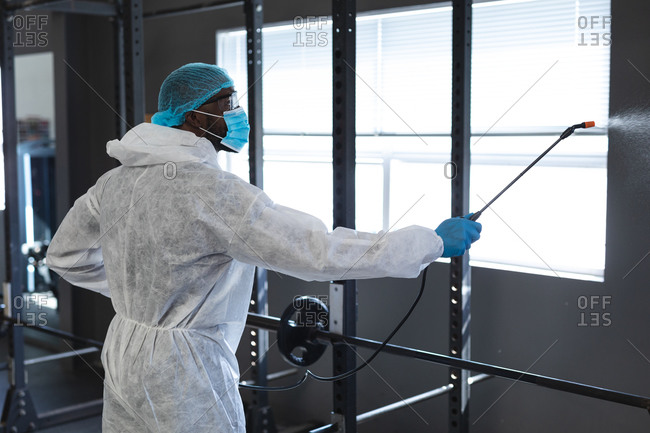 Male worker wearing protective clothes and face masks cleaning the gym using disinfectant.