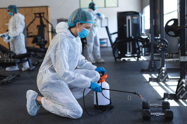 Female worker wearing protective clothes and face masks cleaning the gym using disinfectant.