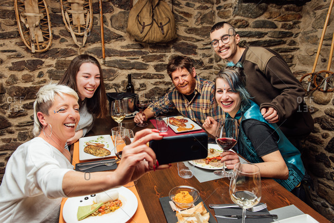 High angle of delighted company of hipsters gathering at table with food in restaurant and taking photo on selfie camera of smartphone