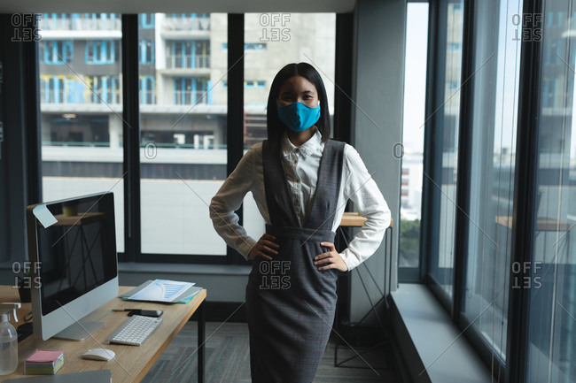 Portrait of Asian woman wearing face mask standing with hands on her hips in modern office.