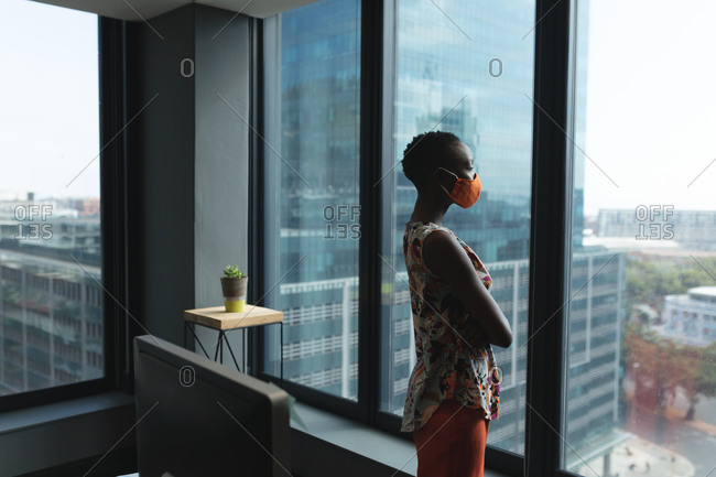 African American woman wearing face mask looking out of the window at modern office.