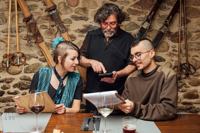 Cheerful couple of hipsters sitting at wooden table with menu and talking to waiter while ordering food during date in cafe