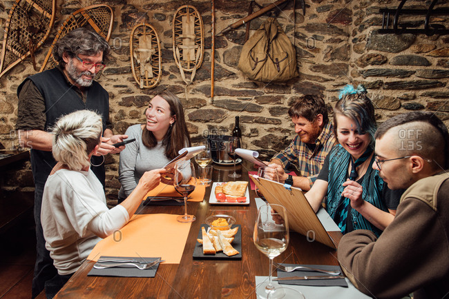 Cheerful group of hipsters sitting at wooden table with menu and talking to waiter while ordering food during date in cafe