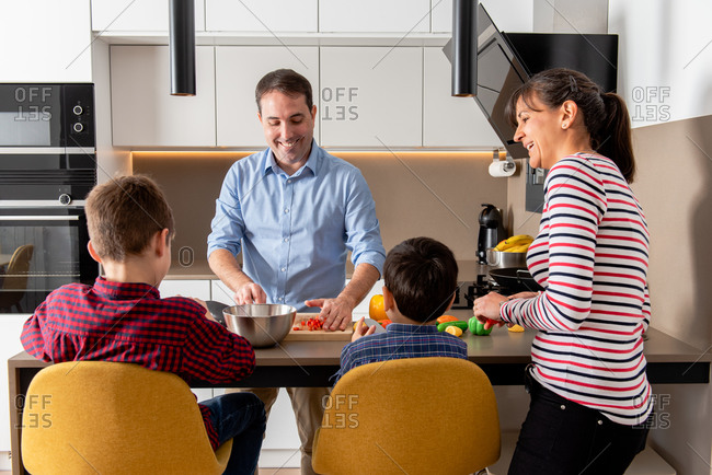 Cheerful family gathering in modern equipped kitchen while cutting vegetables and cooking lunch together