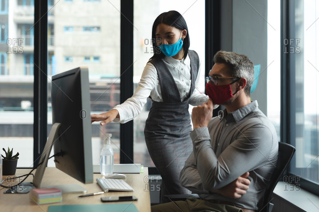 Diverse male and female colleagues wearing face masks working together at modern office.