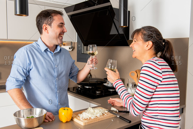 Joyful couple wearing casual outfits enjoying white wine and looking at each other with happy smile while cooking dinner together in modern kitchen
