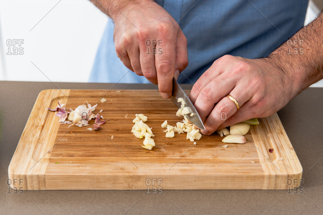 Crop anonymous male cook in casual shirt chopping aromatic garlic on cutting board in light kitchen