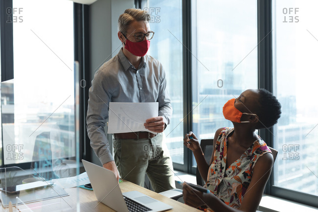 Diverse male and female colleagues wearing face masks talking to each other at modern office.