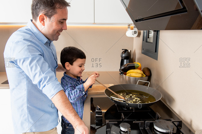 Side view cute concentrated boy stirring garlic on frying pan while learning to cook with father