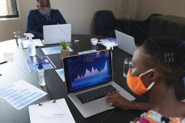 African American woman wearing face mask using laptop in meeting room at modern office.