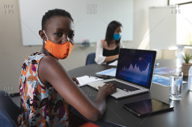 Portrait of African American woman wearing face mask using laptop in meeting room at modern office.