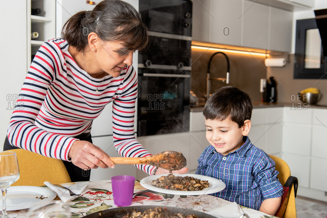 Positive mother in casual wear putting freshly cooked tasty stew on plate for adorable little son in modern kitchen