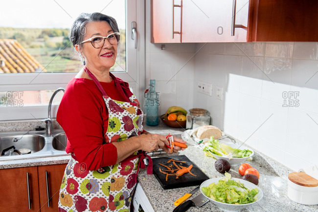 Side view content grandma in apron peeling carrot and looking at camera happily while cooking dinner in contemporary kitchen