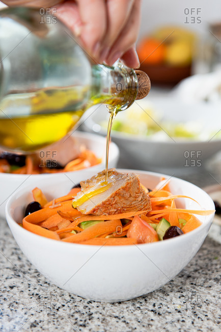Crop unrecognizable female pouring olive oil into bowls with sliced vegetables and bacon in light kitchen