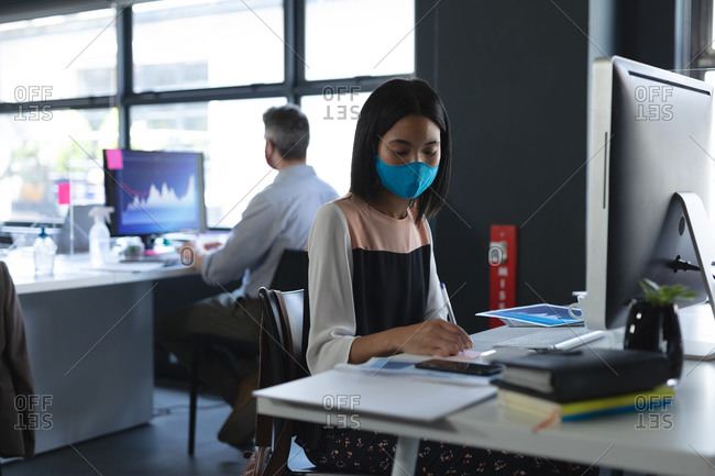 Asian woman wearing face mask using graphic tablet while sitting on her desk at modern office.